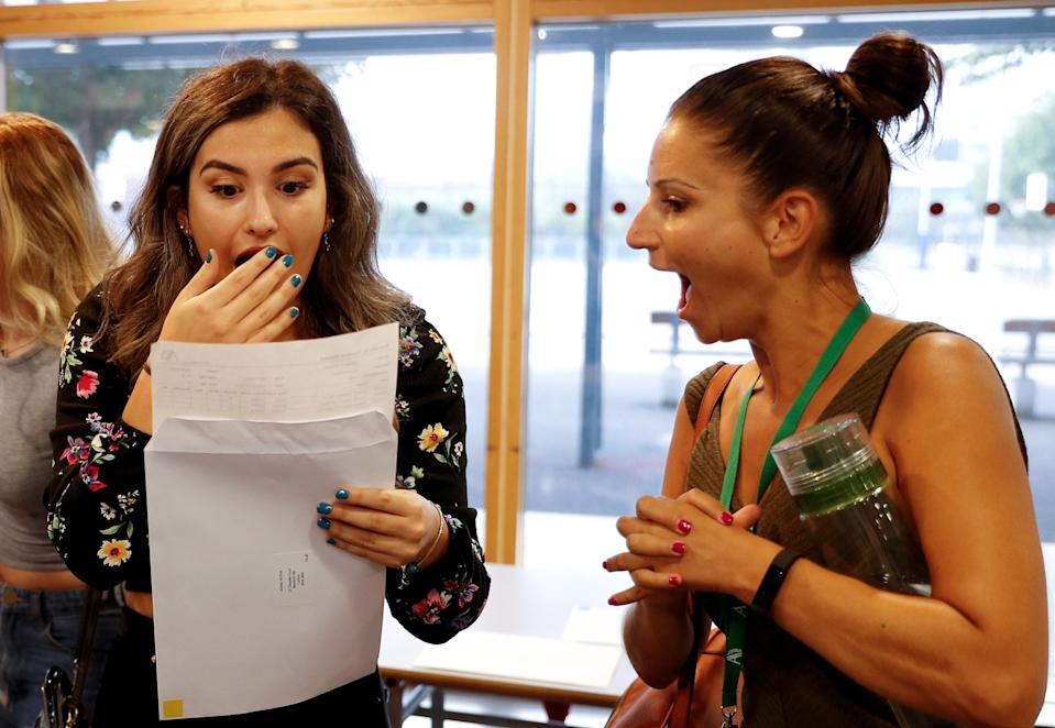 A student and a teacher react as she checks her A-Level results at Ark Academy, amid the spread of the coronavirus disease (COVID-19), in London, Britain August 13, 2020. REUTERS/Peter Nicholls     TPX IMAGES OF THE DAY