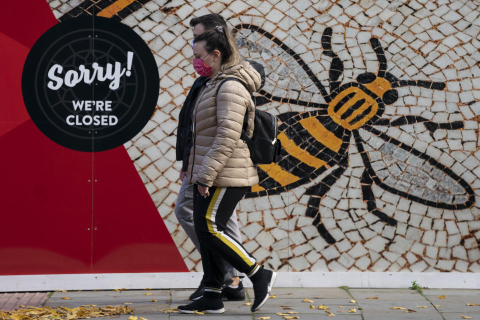 People walk by a sign in Manchester, England, Tuesday, Oct. 20, 2020. The British government appeared poised Tuesday to impose strict coronavirus restrictions on England's second-largest city after talks with officials in Greater Manchester failed to reach an agreement on financial support for people whose livelihoods will be hit by the new measures( AP Photo/Jon Super)