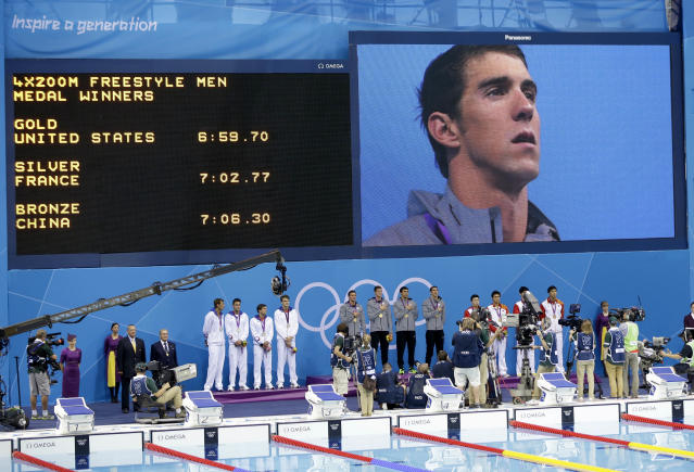 United States' Michael Phelps is seen on a large screen during a medal ceremony for the French, United States and Chinese men's relay teams in the 4 x 200-meter freestyle relay at the Aquatics Centre in the Olympic Park during the 2012 Summer Olympics in London, Tuesday, July 31, 2012. (AP Photo/Lee Jin-man)
