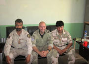 In this undated photo provided by Ryan Brummond, U.S. Special Forces Officer Ryan Brummond, center, is seated next to Mohammad Khalid Wardak, right, in Afghanistan. Khalid, as he's called by his friends, had no intention of leaving Afghanistan, where he was a high-profile national police officer who'd worked alongside American special forces to defeat the Taliban. Then with stunning speed, his government collapsed. Now he is in hiding with his wife and four children, wounded and hunted by the Taliban, desperately hoping that American officials will repay his loyalty by helping his family escape almost certain death. (Ryan Brummond via AP)
