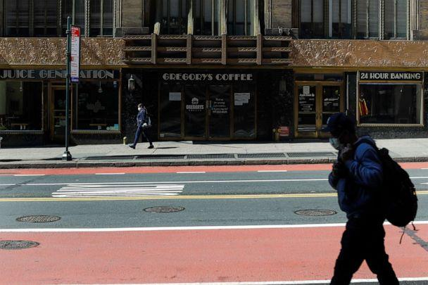 PHOTO: Pedestrians wear protective masks during the coronavirus pandemic as the pass businesses that are closed on 42nd Street, May 15, 2020, N.Y. (Frank Franklin Ii/AP)