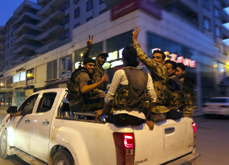Turkish-backed Syrian opposition fighters from the Syrian National Army, flash the V-sign as they are driven through the town of Akcakale, Sanliurfa province, southeastern Turkey, on their way to enter over the border to Tel Abyad, Syria, Friday, Oct. 11, 2019. Turkey's vice president says Turkish troops and their allied Syrian opposition forces have advanced up to 8 kilometers (5 miles) deep into Syrian territory. (AP Photo/Emrah Gurel)