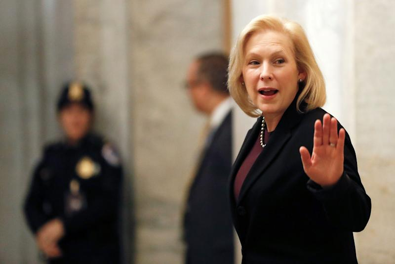 Sen. Kirsten Gillibrand, D-N.Y., waves while arriving at the Capitol in Washington during the impeachment trial of President Donald Trump on Friday.
