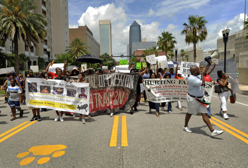 Protesters make their way down Bay Street as they head to the Duval County Jail building to show their support for Marissa Alexander during a protest march in Jacksonville, Fla. on Saturday, July 20, 2013. Several hundred protesters gathered to express a variety of grievances including the verdict in the George Zimmerman trial, the job being done by State Attorney Angela Corey and the sentence received by Marissa Alexander, a Jacksonville woman sentenced to 20 years after firing a warning shot with her gun and claiming self defense from her abusive husband. (AP Photo/The Florida Times-Union, Bob Self)