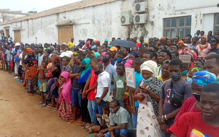People wait for friends and relatives as a ship carrying more than 1,000 people fleeing an attack claimed by Islamic State-linked insurgents on the town of Palma, docks in Pemba, Mozambique, April 1, 2021.