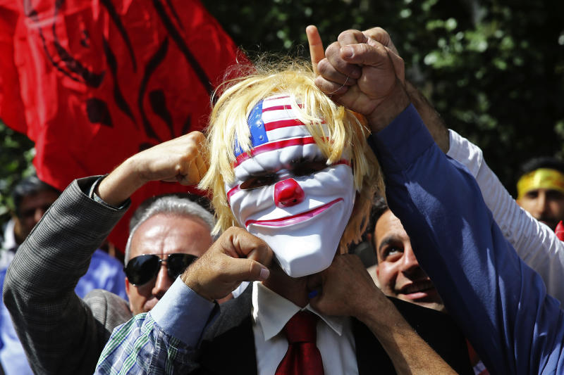 "Iranian protesters pretend to punch a mask which mocks President Donald Trump in a show of anger over the deaths of nearly 60 Palestinians along the Gaza border on Monday, during a protest inside the former U.S. embassy in Tehran, Iran, Wednesday, May 16, 2018. State media reported that Iran's President Hassan Rouhani has condemned the killing of Palestinians by Israel, saying ""Palestinians are fighting for their homeland."" (AP Photo/Ebrahim Noroozi)"