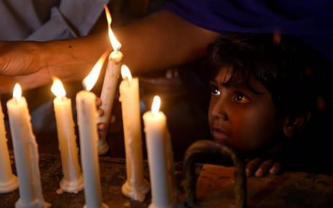 A Pakistani Christian child looks on as adults light candles to pay tribute to Sri Lankan blasts victims - Credit: Rizwan Tabassum/AFP