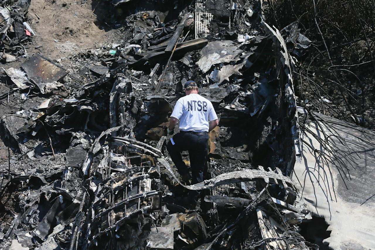 A National Transportation Safety Board official looks through the wreckage at the scene Monday, June 2, 2014, in Bedford, Mass., where a plane plunged down an embankment and erupted in flames during a takeoff attempt at Hanscom Field on Saturday night. Lewis Katz, co-owner of The Philadelphia Inquirer, and six other people died in the crash. (AP Photo/Boston Herald, Mark Garfinkel, Pool)