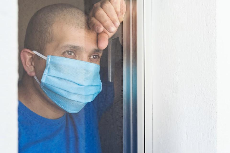 Sick man with face mask looking out the window being quarantined at home