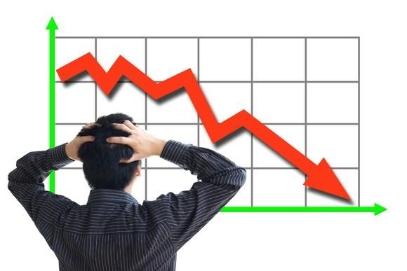 A person staring at a red arrow on graph trending sharply downward.