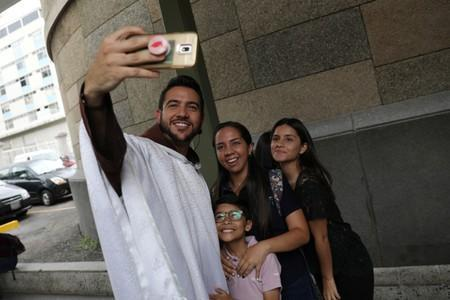 Venezuelan priest Luis Antonio Salazar uses a mobile phone to take a selfie with devotees after Sunday Mass at Chiquinquira church in Caracas