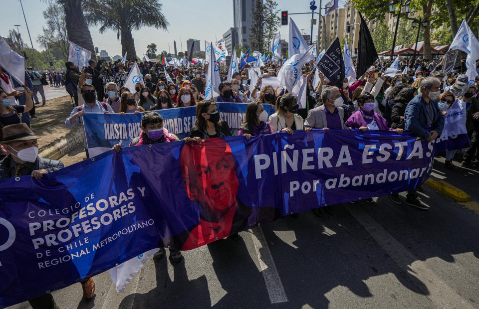 """Teachers on strike carry a banner depicting Chilean President Sebastian Piñera and the Spanish message """"Pinera you flunked for abandoning the teachers"""" as they call for his resignation in connection with his name listed in the """"Pandora Papers"""" in Santiago, Chile, Wednesday, Oct 13, 2021. Some teachers went on a one-day strike Wednesday after the president vetoed legislation on Oct. 6 that would have been beneficial to teachers in the areas of evaluations and retirement. (AP Photo/Esteban Felix)"""
