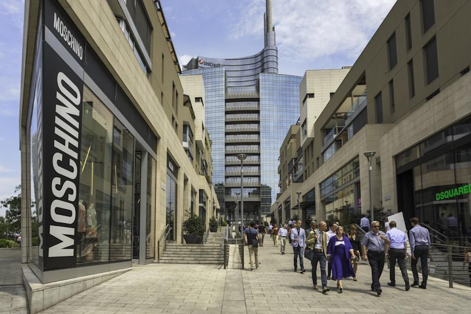 People walking down a street lined with stores and restaurants in the modern Porta Nuova district of Milan.