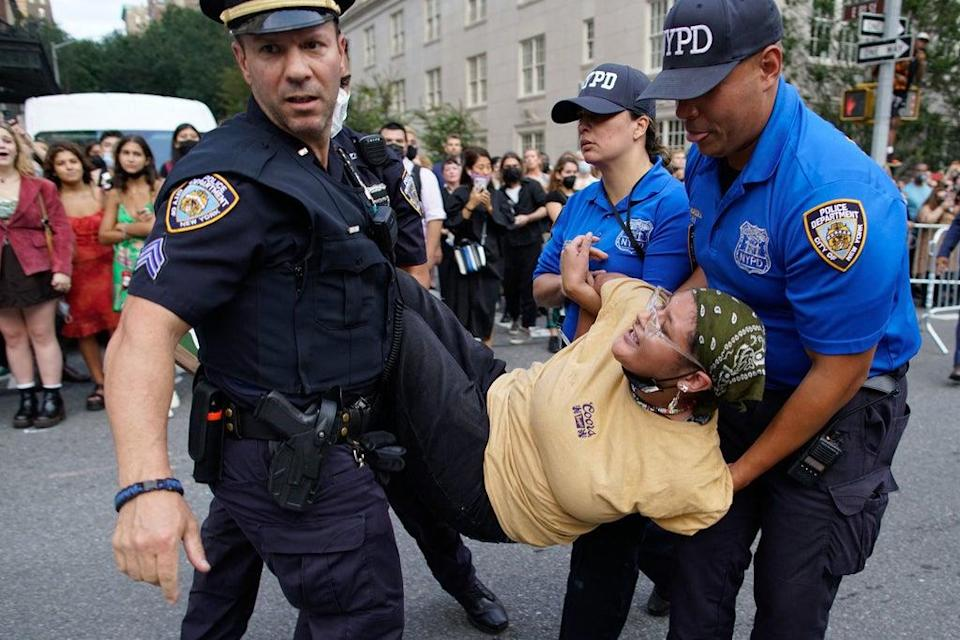Protestor seen being carried away after demonstration in front of Met Gala (AFP via Getty Images)