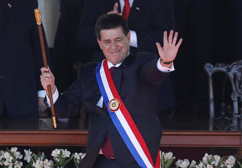Paraguay's New President Horacio Cartes waves holding the presidential baton and wearing the presidential sash during his swearing-in ceremony at Palacio de Lopez presidential palace in Asuncion, Paraguay, Thursday, Aug. 15, 2013. (AP Photo/Jorge Saenz)