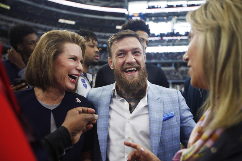Susan G. Komen for the Cure founder Nancy Brinker, left, and UFC fighter Conor McGregor, center, react on the sideline before an NFL football game between the Dallas Cowboys and the Jacksonville Jaguars in Arlington, Texas, Sunday, Oct. 14, 2018. (AP Photo/Jim Cowsert)