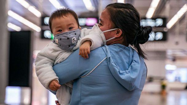 PHOTO: A woman carries a baby wearing a protective mask as they exit the arrival hall at Hong Kong High Speed Rail Station on Jan. 29, 2020. (Anthony Kwan/Getty Images)