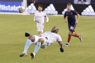 New England Revolution defender Andrew Farrell (2) flips back to kick the ball during the first half of an MLS soccer match against the Chicago Fire in Chicago, Saturday, April 17, 2021. (AP Photo/Mark Black)