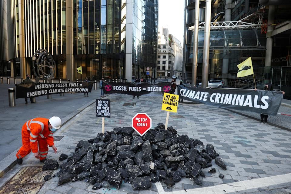 <p>Activists  hold banners as they stand next to fake coal</p> (REUTERS)