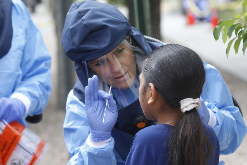 In this May 14, 2020, photo, Salt Lake County Health Department public health nurse Lee Cherie Booth performs a COVID-19 test outside the Salt Lake County health department, in Salt Lake City. People who test positive are logged into an online database and assigned as new case to contract tracers at the health department who call them to find out who they've been around and where they've been. (AP Photo/Rick Bowmer)
