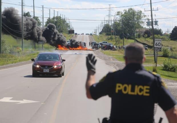 An Ontario Provincial Police officer guides a car past the blockade on Argyle Street, south of Caledonia, last summer. The area is the subject of an ongoing land battle between the Six Nations of the Grand River and local developers.