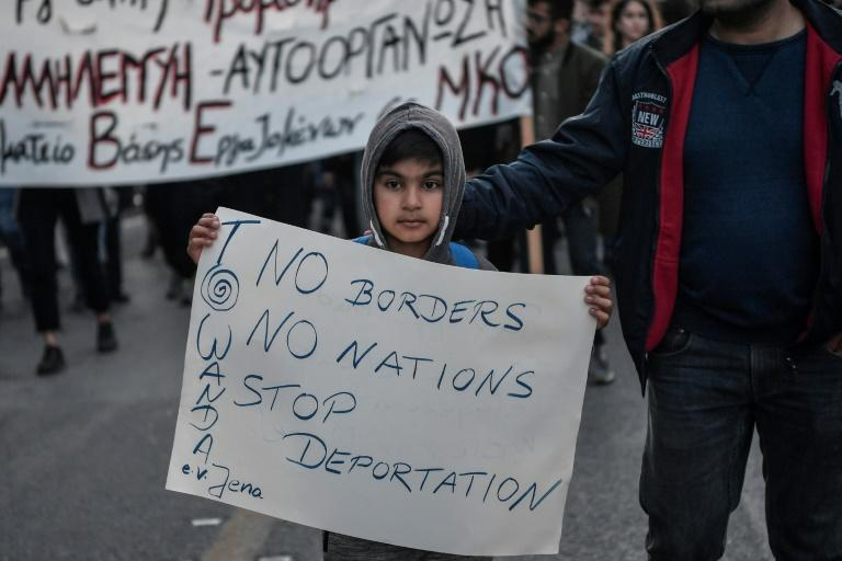 "A refugee child holds a placard reading ""No borders no nations stop deportation"" at a demonstration in Athens to ask for funding for the EU ESTIA emergency support package which provides urban accommodation and cash assistance to refugees and asylum-seekers in Greece"