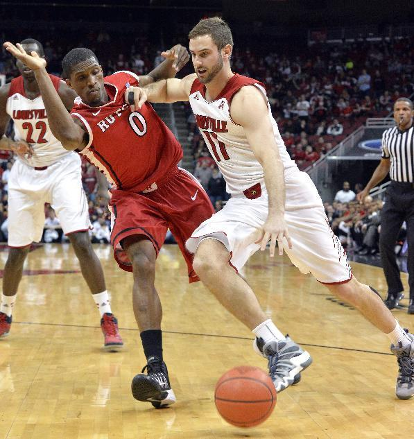 Louisville's Luke Hancock, right, attempts to drive around the defense of Rutgers' Malick Kone during the second half of an NCAA college basketball game Sunday, Feb. 16, 2014, in Louisville, Ky. Louisville won 102-54. (AP Photo/Timothy D. Easley)