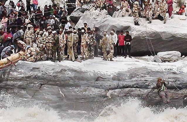"In this handout photograph received from the Indo Tibetan Border Police (ITBP) on June 24, 2013 members of the ITBP rescue stranded villagers along a rope bridge fixed across the Alaknanda river at Lambagad en route to Badrinath. Around 1,000 people have been killed in flash floods and landslides in northern India, as heavy rains halted the search on June 24 for thousands of tourists still stranded in the devastated Himalayan regions, officials said. AFP PHOTO/ITBP ----EDITORS NOTE---- RESTRICTED TO EDITORIAL USE - MANDATORY CREDIT - ""AFP PHOTO / ITBP"" - NO MARKETING NO ADVERTISING CAMPAIGNS - DISTRIBUTED AS A SERVICE TO CLIENTS-----"