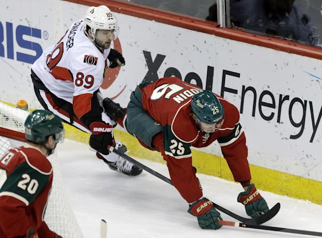 Minnesota Wild's Jonas Brodin, right, of Sweden, is tripped up by Ottawa Senators' Cory Conacher as they chase the puck behind the net in the first period of an NHL hockey game, Tuesday, Jan. 14, 2014, in St. Paul, Minn. (AP Photo/Jim Mone)