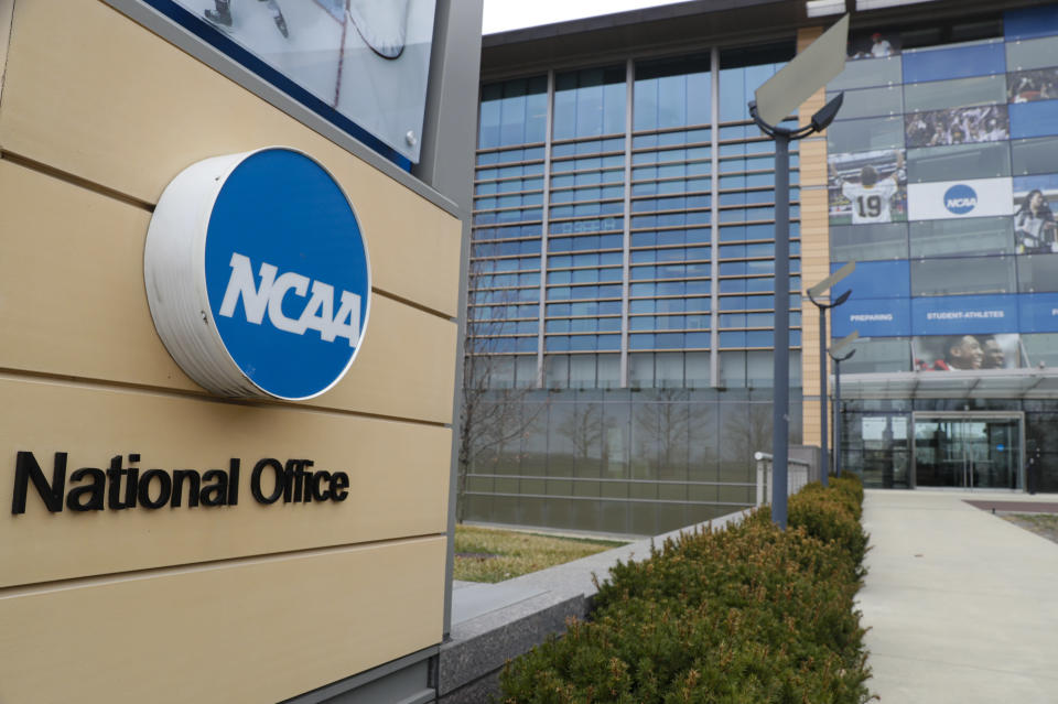 """FILE - This is a March 12, 2020, file photo showing NCAA headquarters in Indianapolis. The NCAA Board of Governors called for a special constitutional convention in November to initiate dramatic reform in the governance of college sports that could be in place as soon as January. The NCAA said it wants to """"reimagine"""" how to more effectively manage the needs of college athletes.(AP Photo/Michael Conroy, File)"""