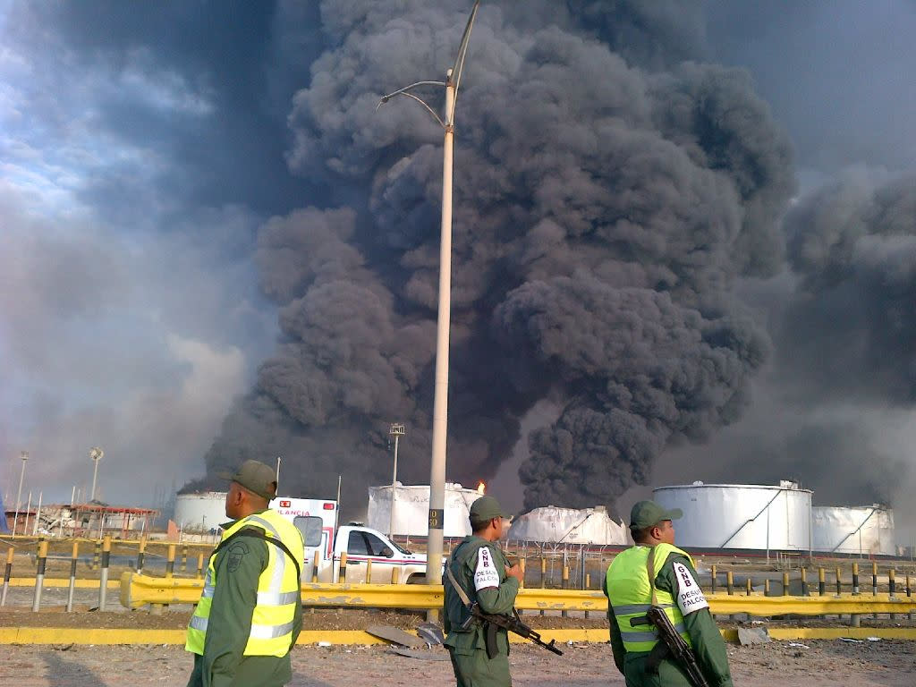 Large plumes of smoke rise from the Amuay refinery as national guards soldiers watch near Punto Fijo, Venezuela, Saturday, Aug. 25, 2012. A huge explosion rocked Venezuela's biggest oil refinery, killing and injuring dozens, an official said. (AP Photo/Abisaid Cermeno)