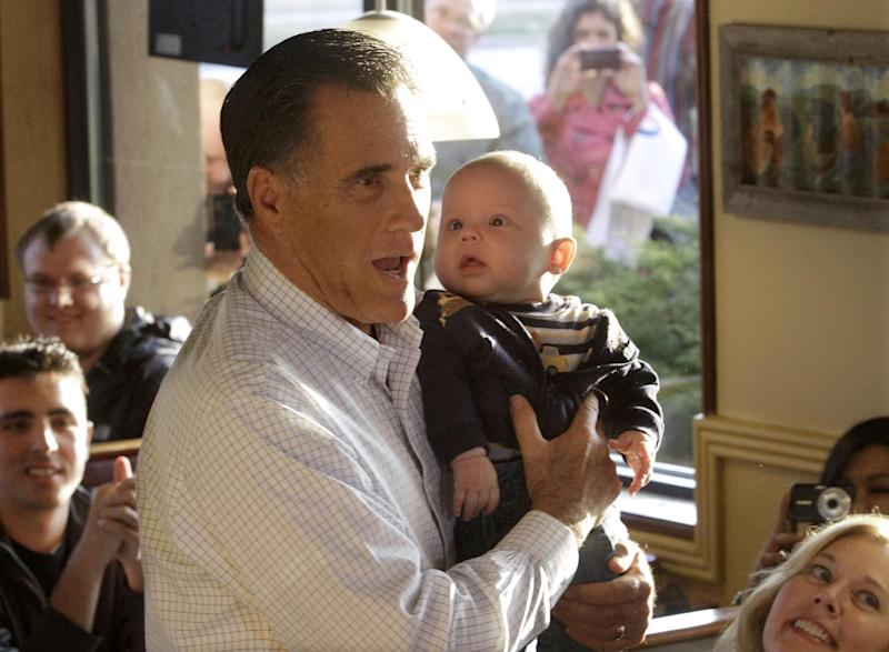 Republican presidential candidate, former Massachusetts Gov. Mitt Romney holds four-month-old Ryan Pratt while campaigning at Pancakes Eggcetera, Friday, March 16, 2012, in Rosemont, Ill. (AP Photo/Seth Perlman)