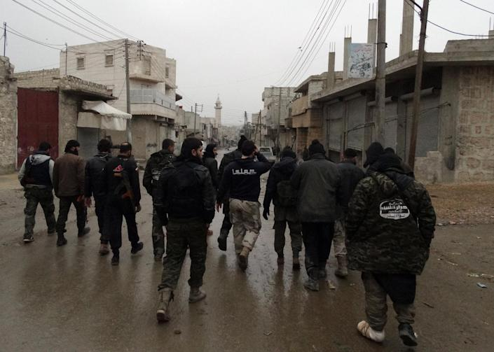 Opposition fighters from the Ahrar Al-Sham brigade walk in Aleppo during ongoing clashes with government forces on January 27, 2014 (AFP Photo/Baraa al-Halabi)