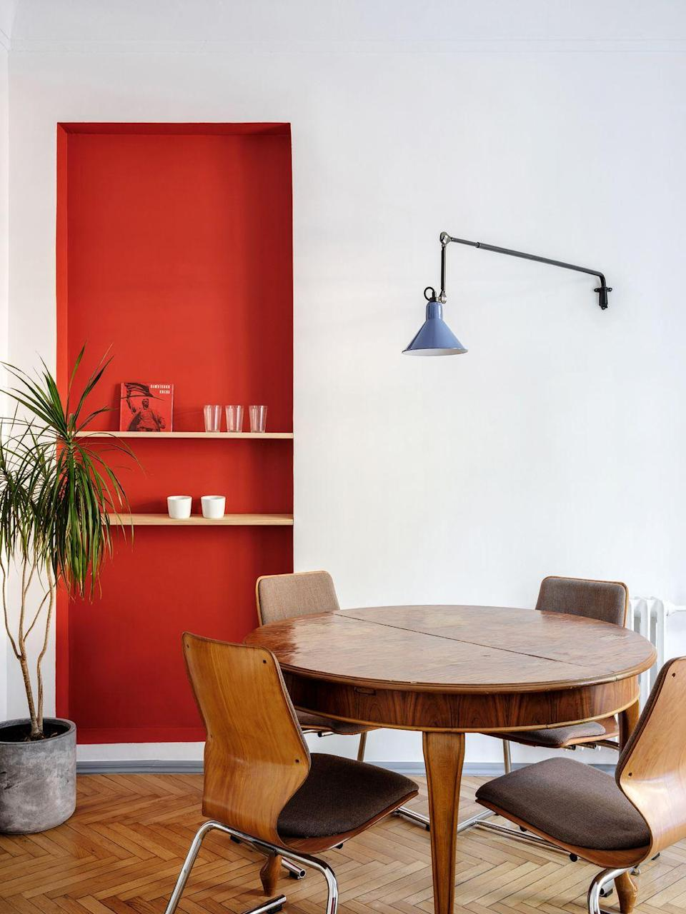 <p>Whether your space has a customized niche or you want to reimagine an existing quirk, consider floating shelves your solution. They'll allow you to get some real practical use of an otherwise unused divot. Here, Emil Dervish made this space pop even more by giving the floating shelves a bright orange-red backdrop. </p>