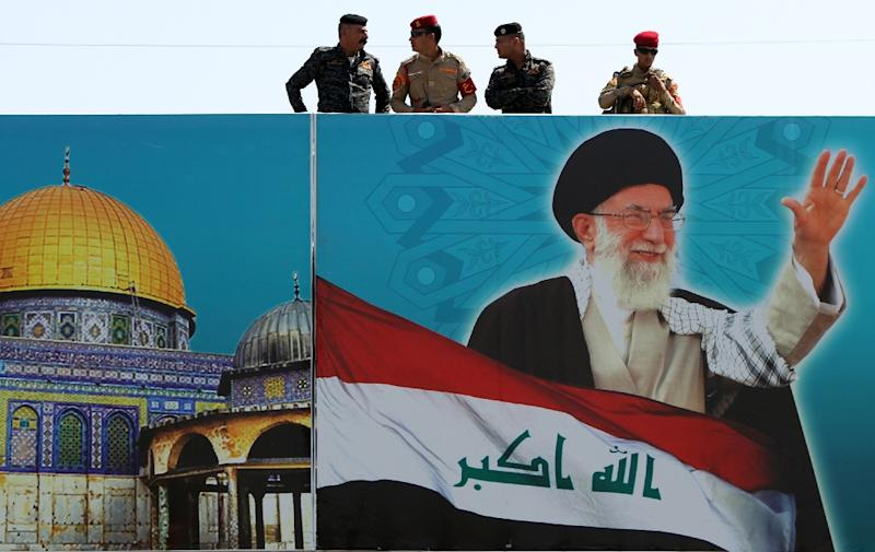 Security forces stand on top of a building covered with a poster of Iran's supreme leader Ayatollah Ali Khamenei and Jerusalem's Dome of the Rock during a rally marking the Quds (Jerusalem) International day in the capital Baghdad, on July 10, 2015 (AFP Photo/Ahmad al-Rubaye)