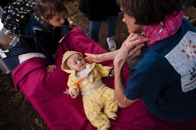A doctor, member of a NGO checks a baby follwing his arrival on Eftalou beach near Molivos village, on the Greek island of Lesbos, after crossing the Aegean sea from Turkey on September 24, 2015 (AFP Photo/Iakovos Hatzistavrou)