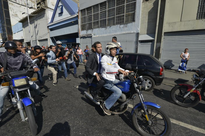 Opposition leader Juan Guaido rides on the back of a motorcycle, toward buses carrying opposition lawmakers that are blocked by security forces, as their group travels to attend a session at the National Assembly in Caracas, Venezuela, Tuesday, Jan. 7, 2020. Venezuela's opposition is facing its biggest test yet after government-backed lawmakers announced they were taking control of what Guaidó supporters have described as the nation's last democratic institution. (AP Photo/Matias Delacroix)