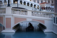 A gondolier steers his boat beneath a quiet pedestrian walkway at the Venetian hotel and casino in Las Vegas, Feb. 4, 2021. The toll of the coronavirus is reshaping Las Vegas almost a year after the pandemic took hold. The tourist destination known for bright lights, big crowds, indulgent meals and headline shows is a much quieter place these days. (AP Photo/John Locher)