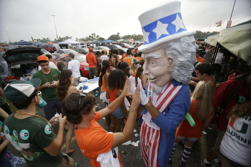 In this Saturday, Nov. 9, 2013 photo, Thomas Vazquez, center left, 18, high-fives an Uncle Sam mascot while tailgating before the start of an NCAA college football game between Miami and Virginia Tech, in Miami Gardens, Fla. It may be the hottest tailgate party at the University of Miami's homecoming game, but the 100-yard stretch of free pizza and party tents set up by Generation Opportunity, a national conservative organization, is also a carefully crafted strategy aimed at getting students to opt out of President Barack Obama's controversial new health law. (AP Photo/Wilfredo Lee)