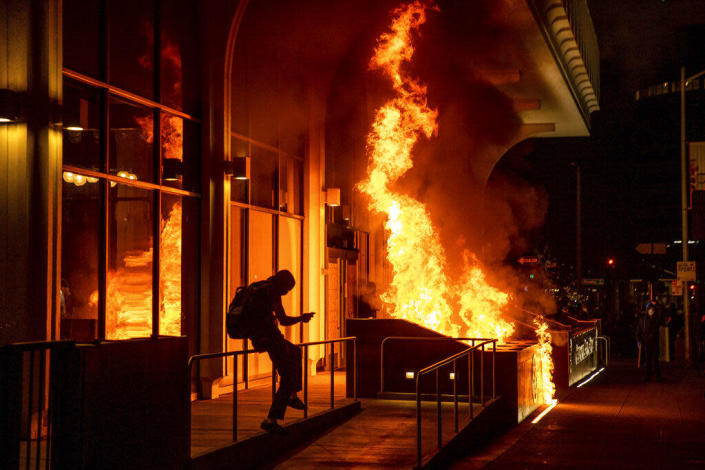 Demonstrators set fire to the front of the California Bank and Trust building during a protest against police brutality in Oakland, April 16, 2021. / Credit: Ethan Swope  P