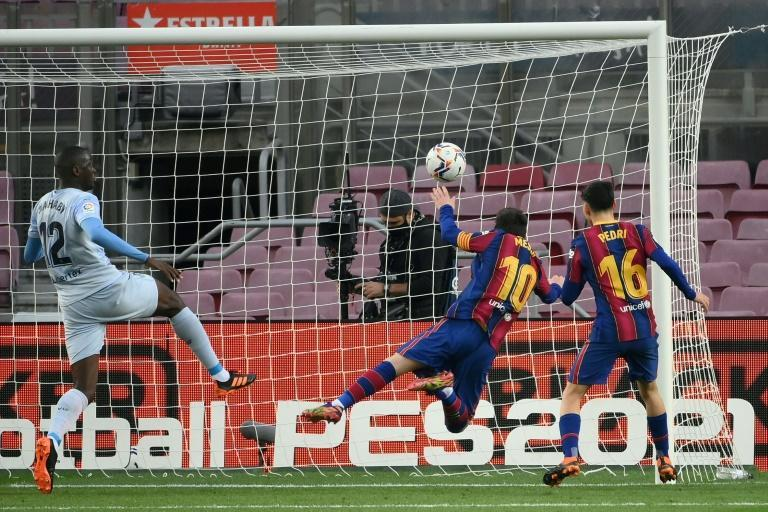 Great leveller: Lionel Messi heads in against Valencia to equal Pele's record for goals scored for one club
