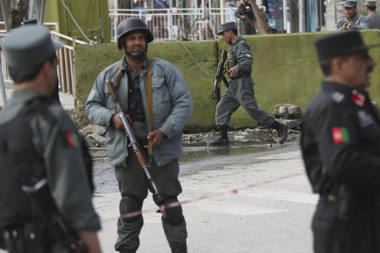 Afghan police men block the street after a suicide bomber wearing a military uniform struck the entrance gate of the Interior Ministry compound in Kabul, Afghanistan, Wednesday, April 2, 2014. Ministry of Interior spokesman Sediq Sediqqi said the bomber, who was wearing a military uniform to evade security checks, reached the entrance of the heavily fortified ministry compound before detonating his explosives. (AP Photo/Massoud Hossaini)
