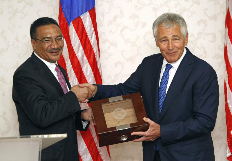 U.S. Defense Secretary Chuck Hagel, right, and Malaysian Defense Minister Hishammuddin Hussein shake hands as they exchange gifts after a joint press conference in Kuala Lumpur, Malaysia, Sunday, Aug. 25, 2013. Hagel is on a three-day visit to Malaysia. (AP Photo/Lai Seng Sin)