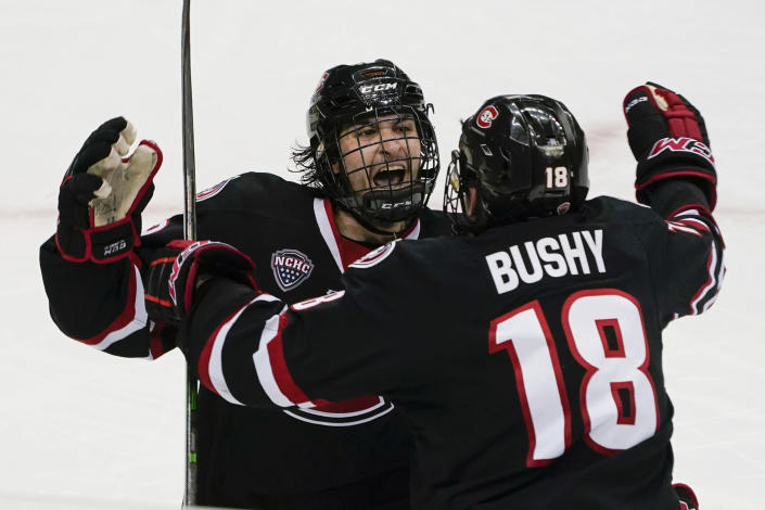 St. Cloud State's Joe Molenaar, left, celebrates with Brendan Bushy (18) after scoring the tying goal against Minnesota State during the third period of an NCAA men's Frozen Four hockey semifinal in Pittsburgh, Thursday, April 8, 2021. St. Cloud State won 5-4 to advance to the championship game Saturday. (AP Photo/Keith Srakocic)