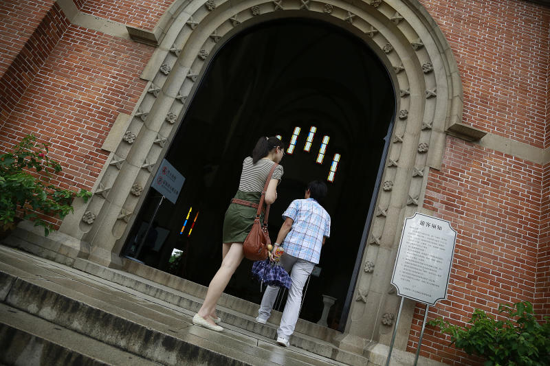 Visitors walk in Sheshan seminary Wednesday July 11, 2012 on the outskirts of Shanghai, China. Newly ordained Chinese bishop Ma Daqin has been placed in isolation after announcing he's quitting his government posts in a challenge to Beijing's control over the Catholic clergy, a Hong Kong church activist and Catholic websites said Tuesday. Ma was being confined at the seminary without contact with others, according to the sources. (AP Photo/Eugene Hoshiko)