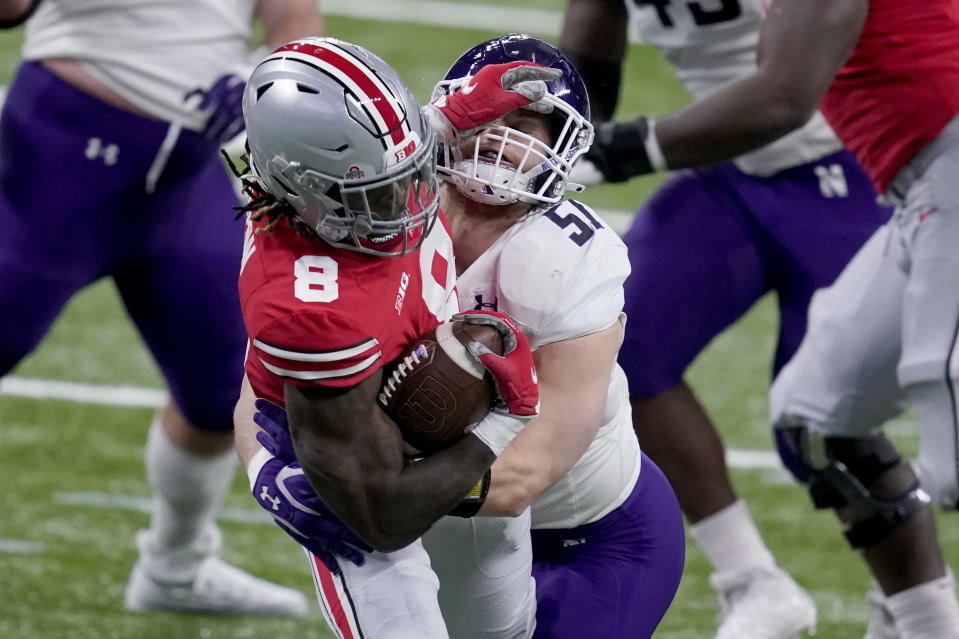 Ohio State running back Trey Sermon (8) runs with the ball as Northwestern linebacker Blake Gallagher (51) defends during the first half of the Big Ten championship NCAA college football game, Saturday, Dec. 19, 2020, in Indianapolis. (AP Photo/Darron Cummings)