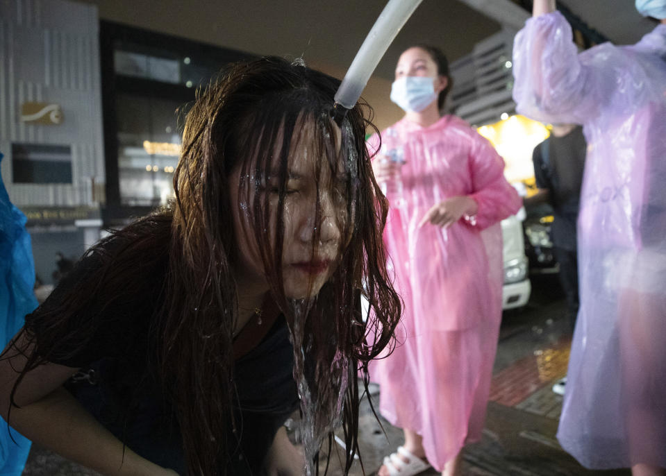 FILE - In this Oct. 16, 2020, file photo, a demonstrator washes her face after police water cannons dispersed them from a protest venue in Bangkok, Thailand. Fed up with an archaic educational system and enraged by the military's efforts to keep control over their nation, a student-led campaign has shaken Thailand's ruling establishment with the most significant campaign for political change in years. (AP Photo/Sakchai Lalit, File)