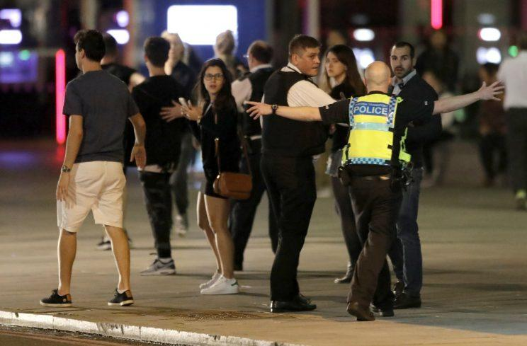 Police urge bystanders to clear the area on London's South Bank (PA)