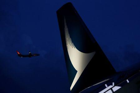 A plane flies behind a new Cathay Pacific Airways Airbus A350 after being received by the airline at Hong Kong Airport May 30, 2016.   REUTERS/Bobby Yip/Files