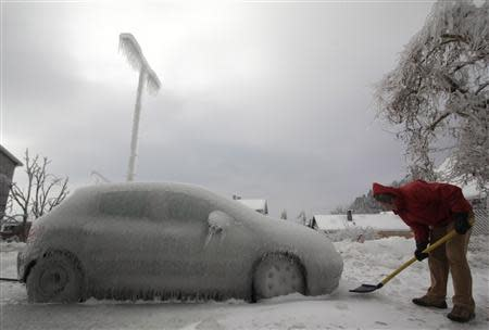 A man shovels ice next to ice-covered car in Postojna